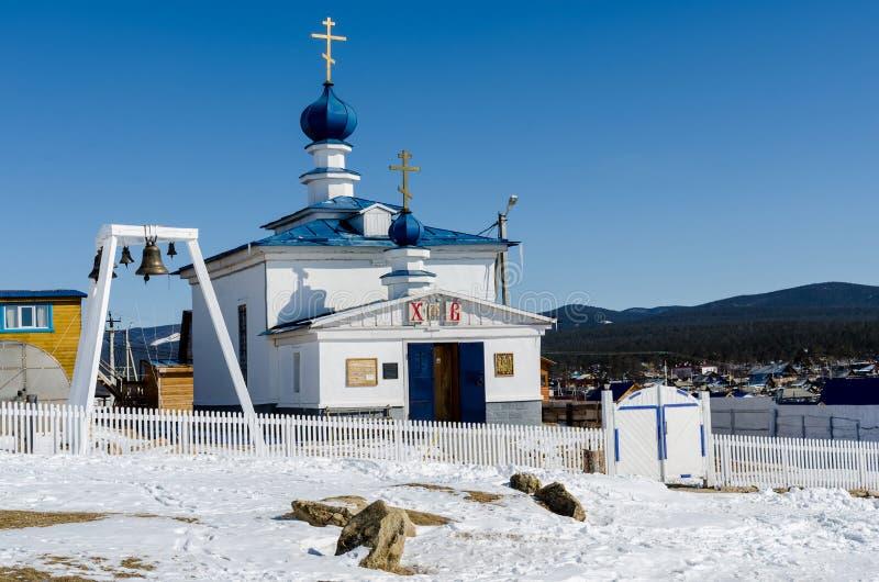 Khuzhir Ryssland - mars, 23, 2013: Vit ortodox kyrka i den Olkhon ön i solig dag för vinter royaltyfri bild