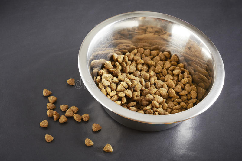 Kibble dog or cat food in bowl. Kibble dog or cat food close up in stainless steel bowl royalty free stock photography