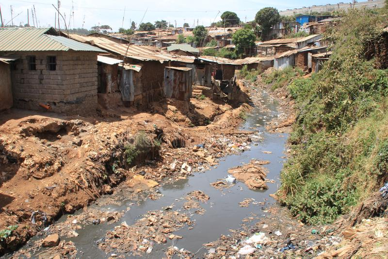 Huge heaps of garbage and a dirty river in the slums of Nairobi - one of the poorest places in Africa. Kibera, Nairobi, Kenya - February 13, 2015: Huge heaps of royalty free stock photography