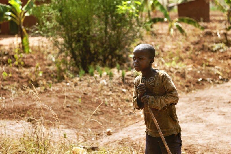 KIBUYE, RWANDA, ÁFRICA - 11 DE SEPTIEMBRE DE 2015: Niño desconocido El niño de African del granjero con su mirada del palillo a t imágenes de archivo libres de regalías