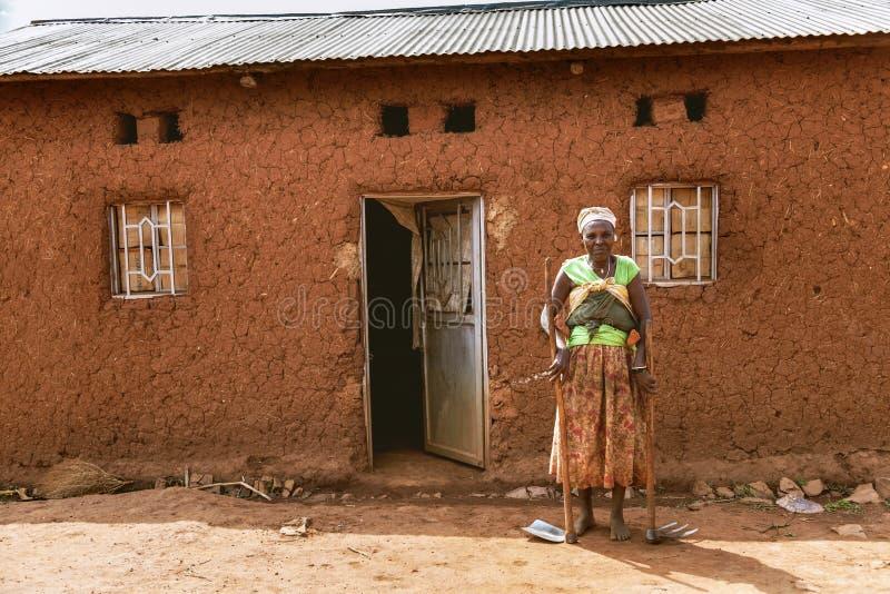 KIBUYE RWANDA, AFRIKA - SEPTEMBER 11, 2015: Okänd kvinna Kvinnan med spetshackan och skyffeln på hennes händer är barfota arkivfoton