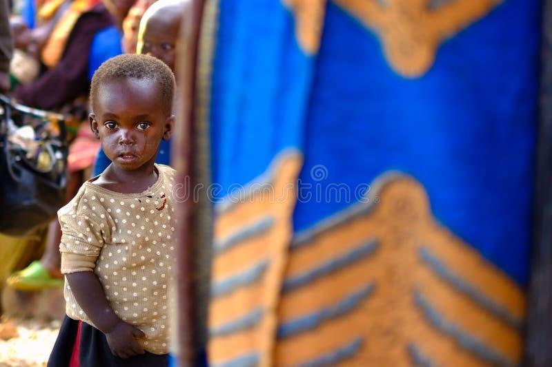 Kibuye/Rwanda - 08/25/2016: Het Afrikaanse meisje verbergen achter moeder stock afbeelding