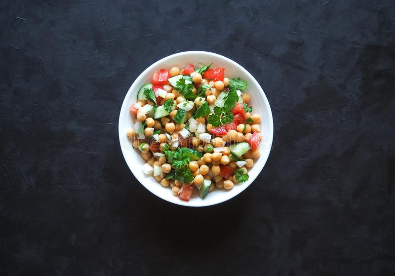 Kichererbsensalat mit Gemüse auf einem schwarzen Hintergrund Sommerpflanzenkost lizenzfreie stockfotos
