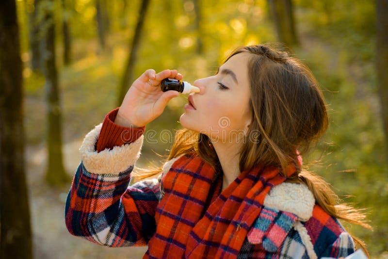 Kichnięcie młoda dziewczyna z nosa wiper wśród żółtych drzew w parku Młoda kobieta podmuchowy nos przy naturą Kobieta robi lekars obrazy royalty free