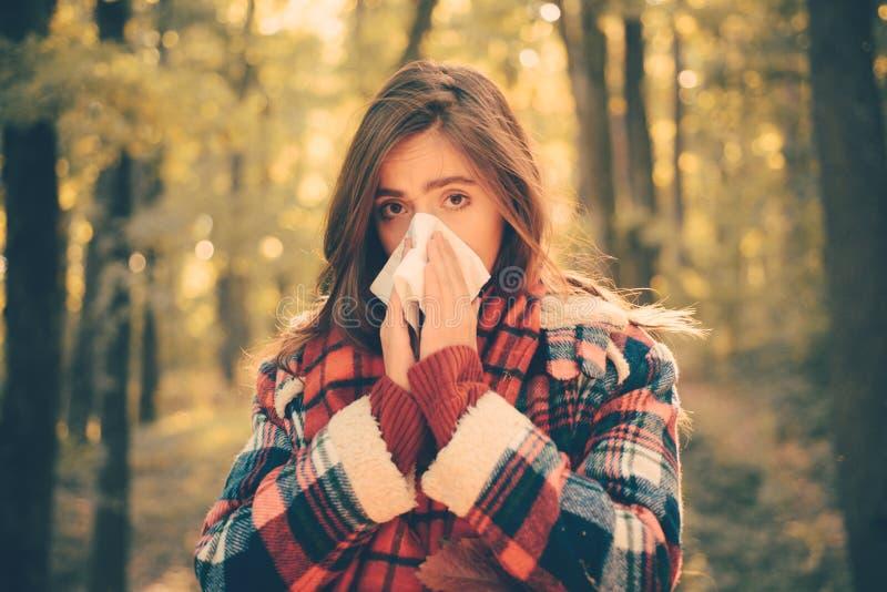 Kichnięcie młoda dziewczyna z nosa wiper wśród żółtych drzew w parku Opieka zdrowotna Młoda kobieta podmuchowy nos przy naturą fe fotografia stock
