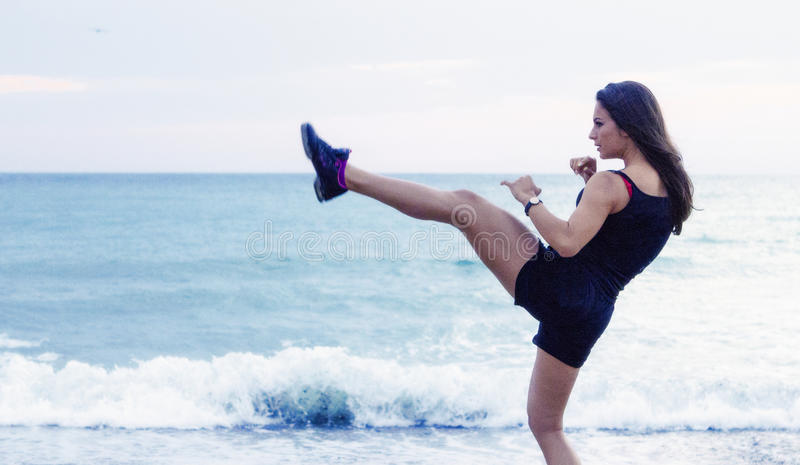 Kick boxing young woman working out on the beach. Young woman doing kick boxing move working out on the beach royalty free stock photography