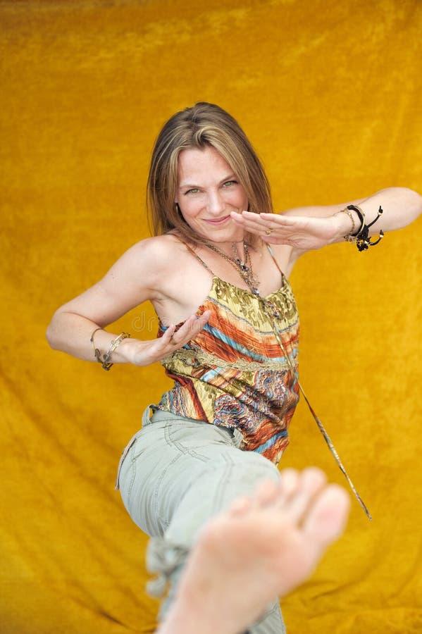 Kick It Girl !. Playful adult woman making a karate kick stock photo