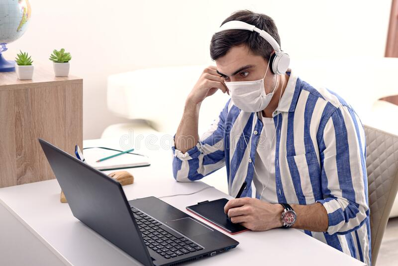 Kick-Mann in medizinischen Masken und Kopfhörer arbeiten auf Laptop, Fernarbeit in Quarantäne, Freelancer-Konzept lizenzfreie stockbilder