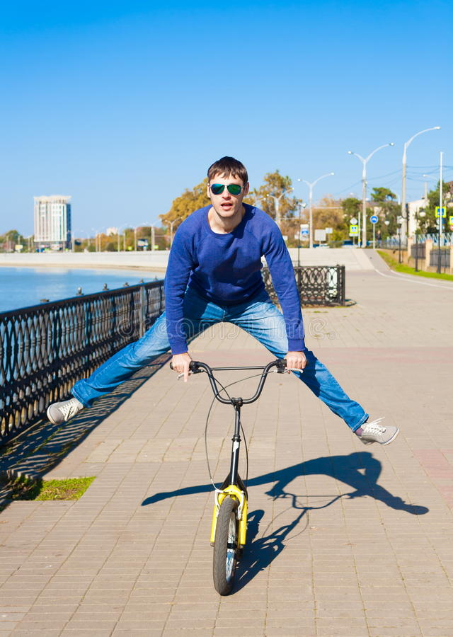 Kick scooter, blue jeans and sweater, full height, smile, jump royalty free stock image