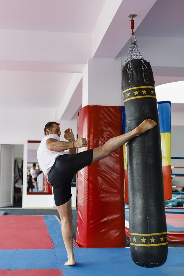 Kickbox在一间健身房的战斗机训练与沙袋,看整体 库存图片