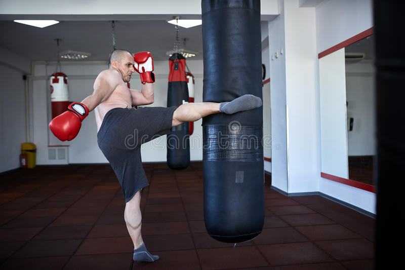 Kickbox fighter working on punchbags stock photos