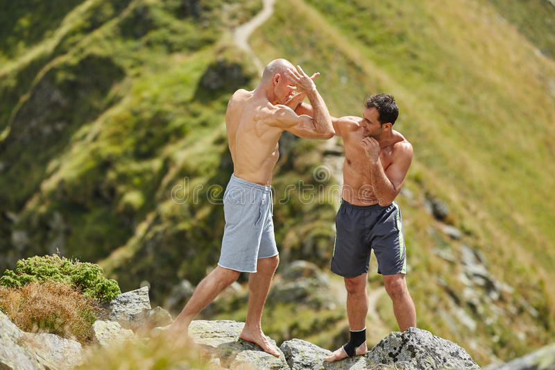 Kickbox fighters sparring in the mountains. Kickboxers or muay thai fighters training in the mountains, sparring royalty free stock photo