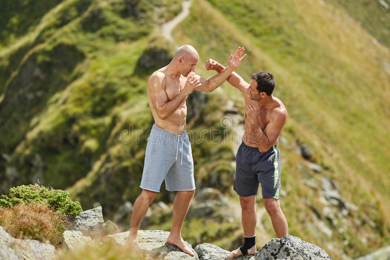 Kickbox fighters sparring in the mountains. Kickboxers or muay thai fighters training in the mountains, sparring royalty free stock image