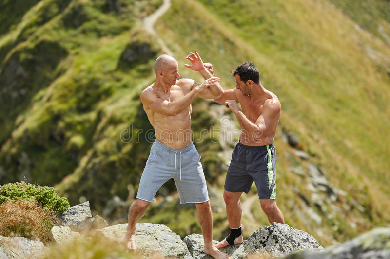 Kickbox fighters sparring in the mountains. Kickboxers or muay thai fighters training in the mountains, sparring stock images
