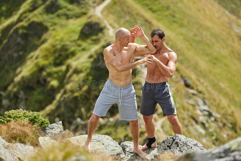 Kickbox fighters sparring in the mountains. Kickboxers or muay thai fighters training in the mountains, sparring stock image