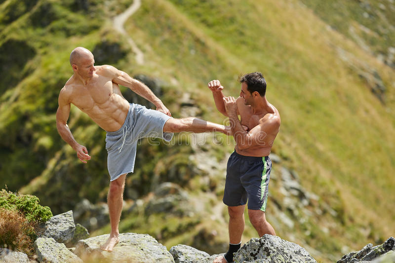 Kickbox fighters sparring in the mountains. Kickboxers or muay thai fighters training in the mountains, sparring stock photos