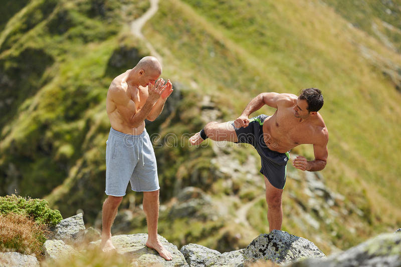 Kickbox fighters sparring in the mountains. Kickboxers or muay thai fighters training in the mountains, sparring stock photography