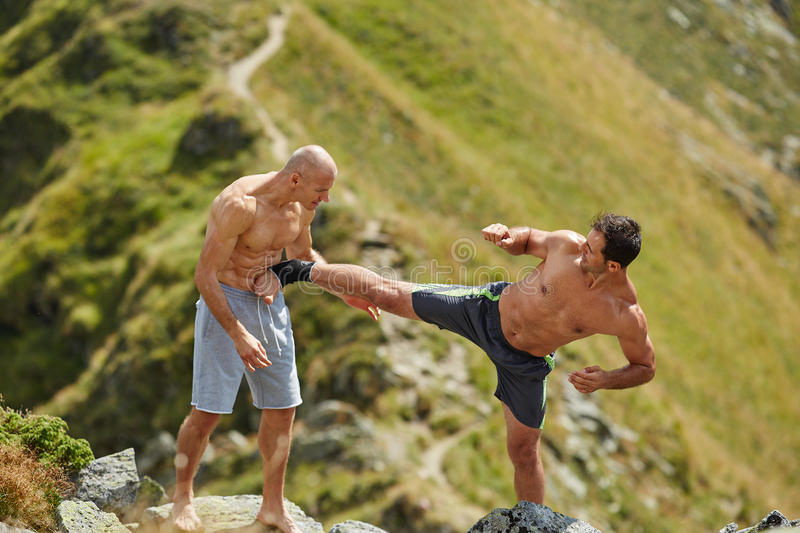 Kickbox fighters sparring in the mountains. Kickboxers or muay thai fighters training in the mountains, sparring royalty free stock photos