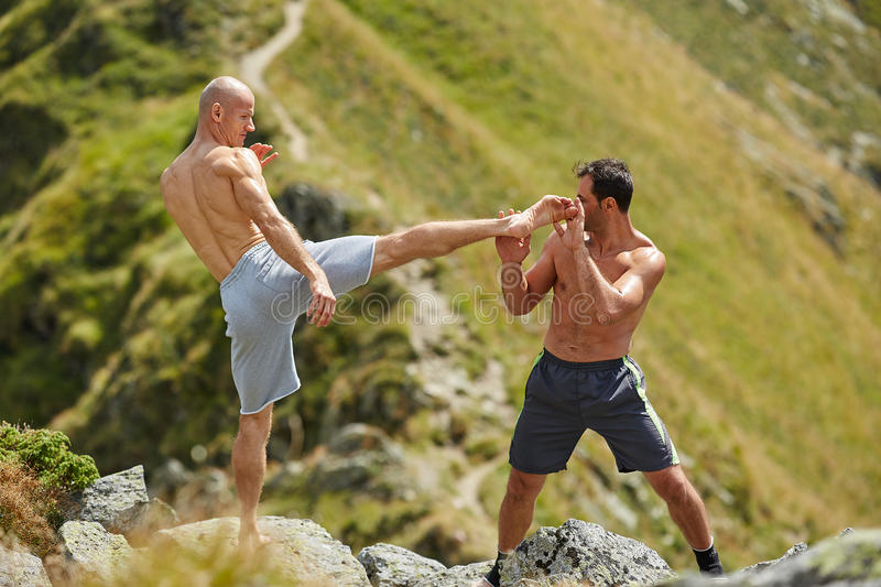 Kickbox fighters sparring in the mountains. Kickboxers or muay thai fighters training in the mountains, sparring royalty free stock photography