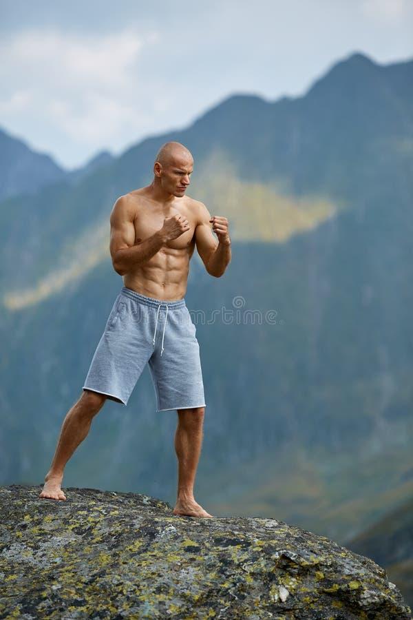 Kickboxer或泰拳战斗机训练在山峭壁 免版税库存图片