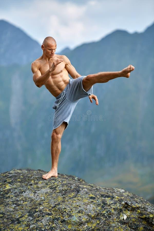 Kickboxer或泰拳战斗机训练在山峭壁 库存图片
