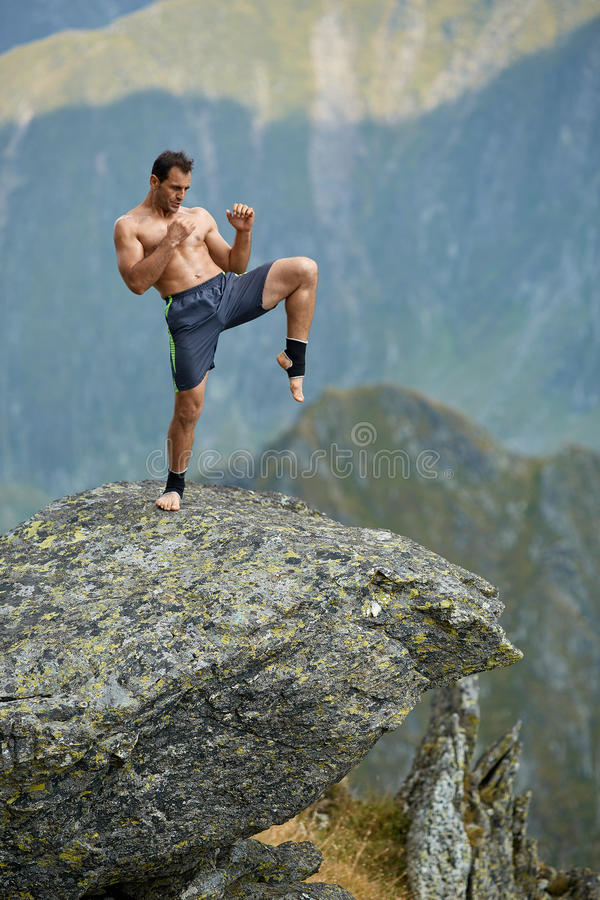 Kickboxer或泰拳战斗机训练在山峭壁 库存照片