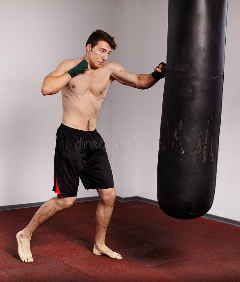Kickboxer com saco de perfurador imagens de stock