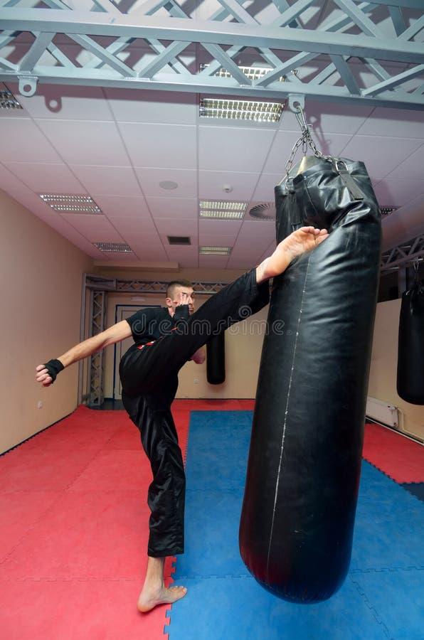 Kickboxer joven que golpea el saco de arena con el pie en gimnasio del deporte imágenes de archivo libres de regalías