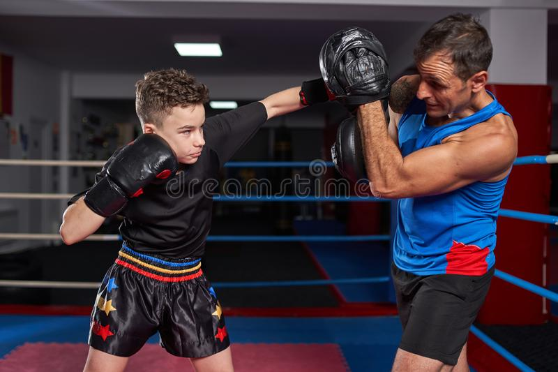 Kickboxer kid and his coach. Young kickbox fighter hitting mitts with his coach royalty free stock image