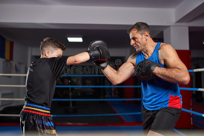 Kickboxer kid and his coach. Young kickbox fighter hitting mitts with his coach royalty free stock photography