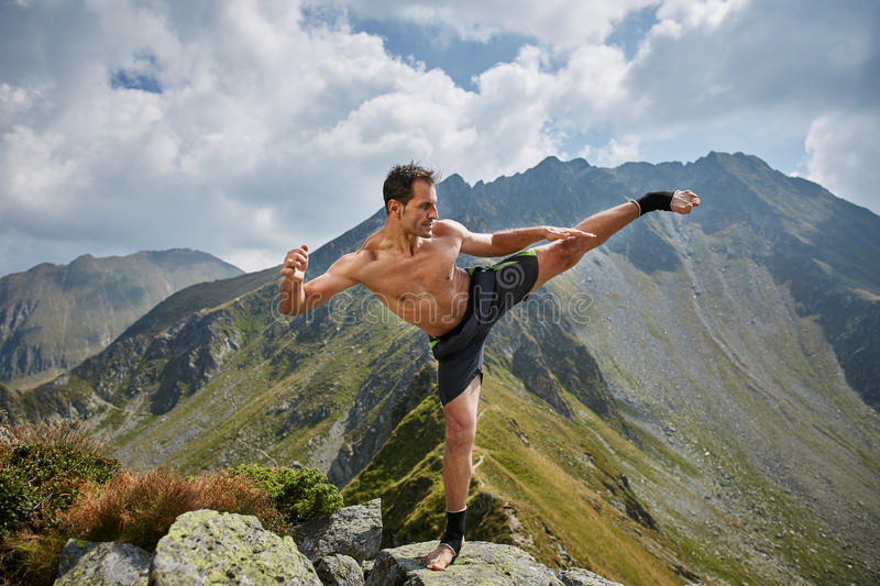 Kickboxer or muay thai fighter training on a mountain. Kickboxer or muay thai fighter practicing shadow boxing on a mountain stock photography