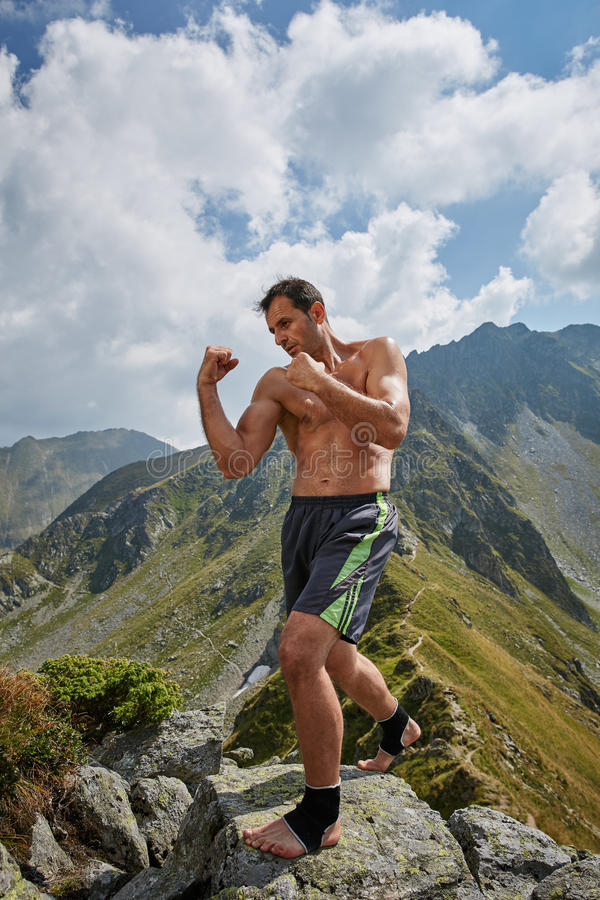 Kickboxer or muay thai fighter training on a mountain. Kickboxer or muay thai fighter practicing shadow boxing on a mountain royalty free stock images