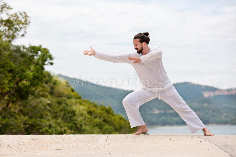 Kickboxer ou homme thaïlandais muay de combattant dans le karaté blanc Wushu de formation sur la montagne images stock