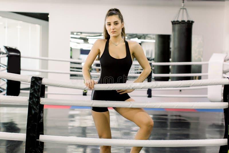 Kickboxermeisje in opleiding Jong geschikt meisje in het zwarte sportkleding stellen in boksring in geschiktheidsgymnastiek royalty-vrije stock fotografie