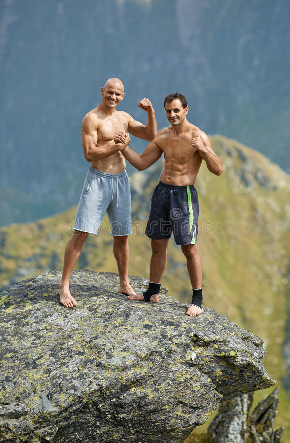 Kickboxers or muay thai fighters on a mountain cliff stock photography