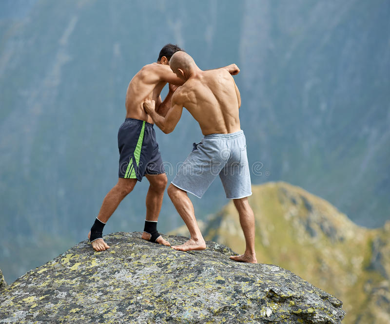 Kickboxers or muay thai fighters training on a mountain cliff. Sparring royalty free stock images