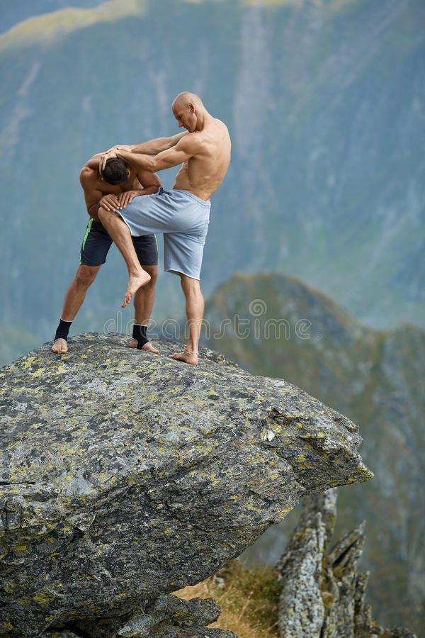 Kickboxers or muay thai fighters training on a mountain cliff. Sparring stock photo