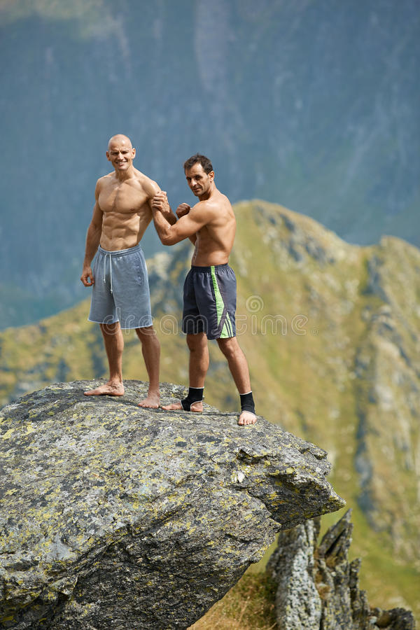 Kickboxers or muay thai fighters training on a mountain cliff. Sparring royalty free stock photos