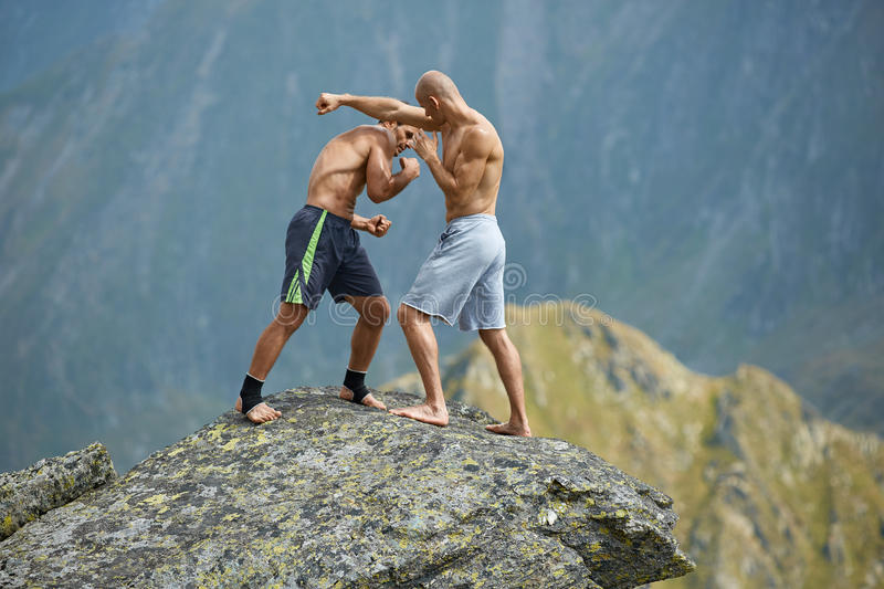 Kickboxers or muay thai fighters training on a mountain cliff. Sparring stock image
