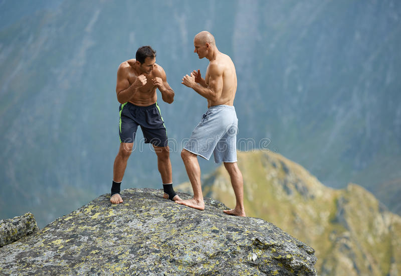 Kickboxers or muay thai fighters training on a mountain cliff. Sparring stock photos