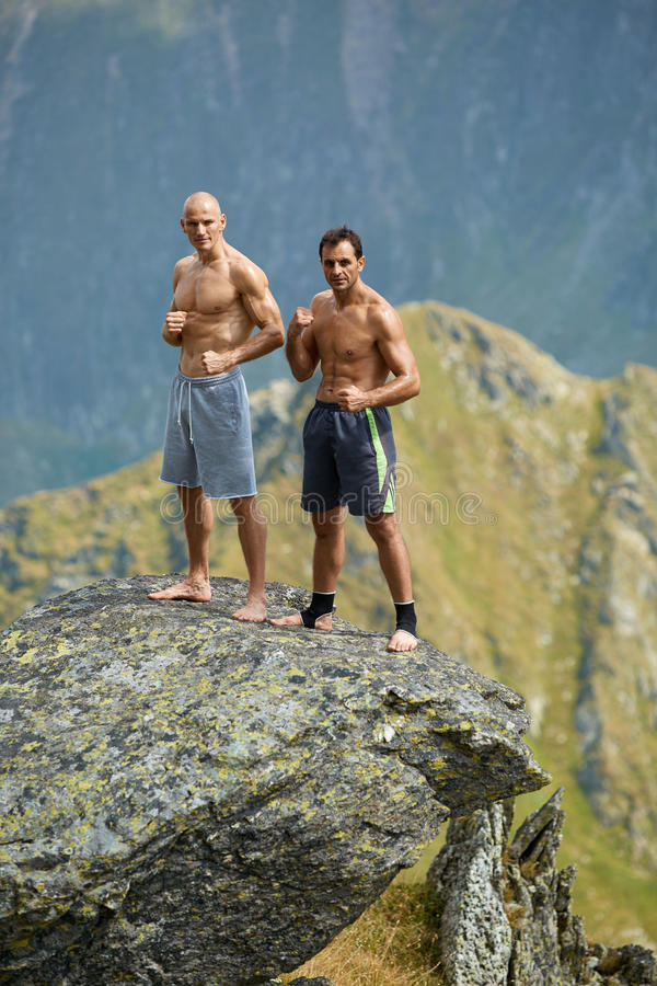 Kickboxers or muay thai fighters training on a mountain cliff. Sparring stock images