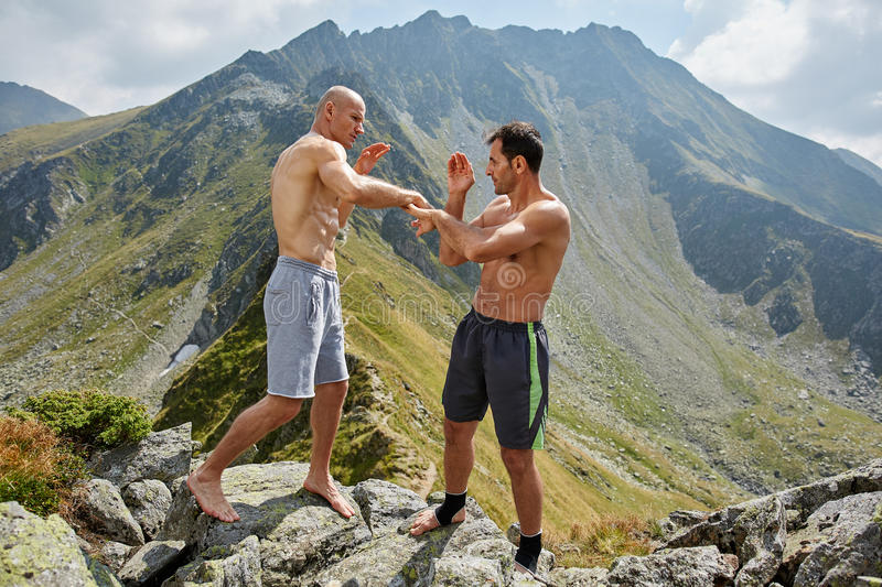 Kickboxers or muay thai fighters training in the mountains. Sparring royalty free stock photo