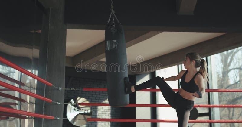 Kickboxing kobiety szkolenie uderza pięścią torbę w sprawności fizycznej pracownianej srogiej siły dysponowanym ciele obrazy royalty free