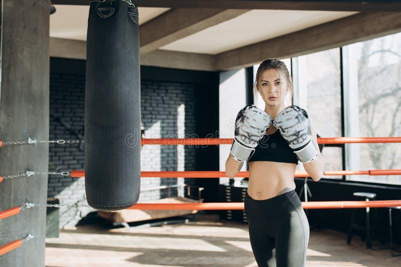 Kickboxing kvinnakämpe för stående som ser säker på idrottskvinnan för tuff kvinnlig kickboxer för kamera som den våldsamma svett arkivfoton