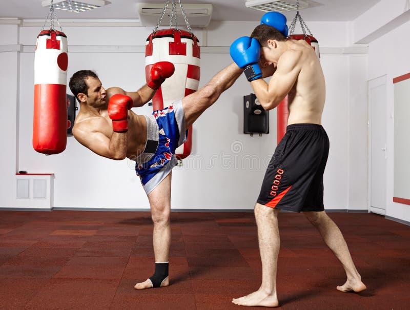 Kickboxvechters die in de gymnastiek sparring stock foto's