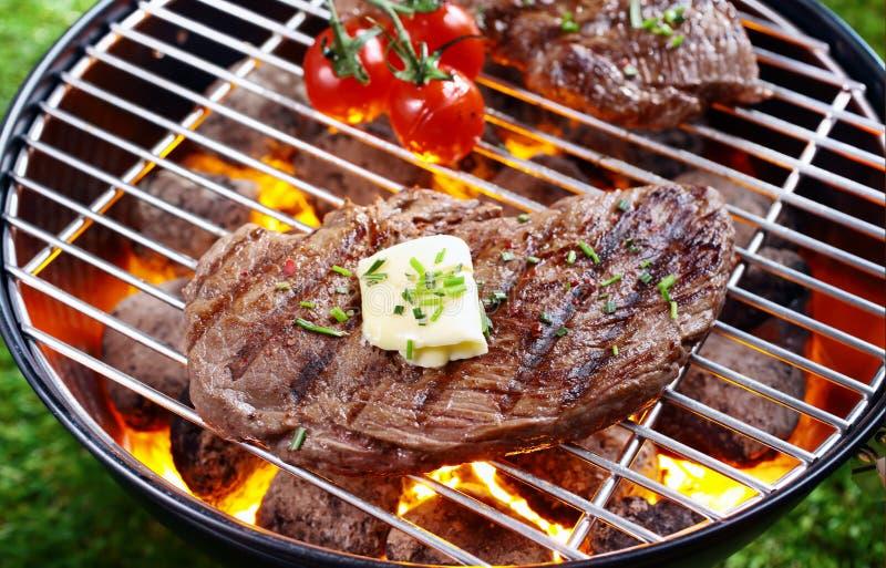 Steak som grillar över glöda, avfyrar arkivfoto