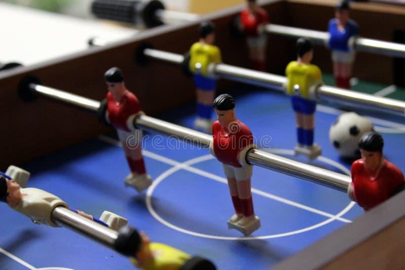 Kicker f?r lek f?r tabellfotbollfotboll sportlagspelare i röda och gula t-skjortor arkivfoton