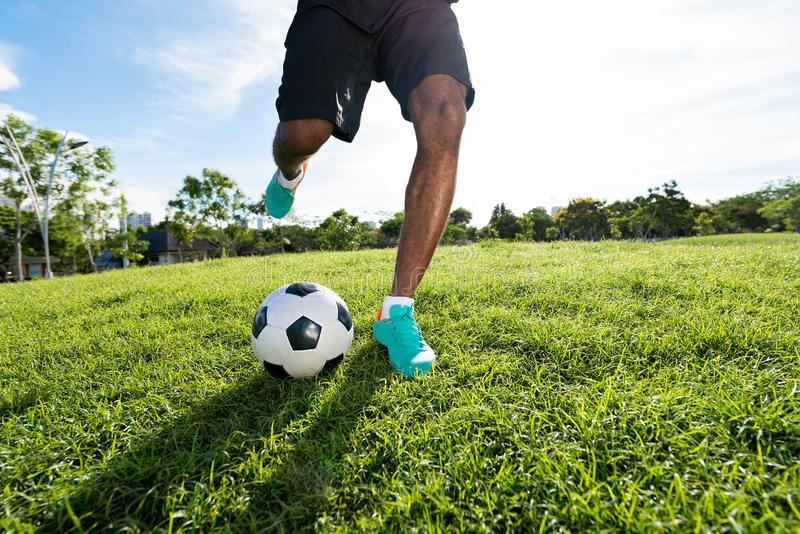 Kicking the ball. Legs of soccer player kicking the ball royalty free stock photos