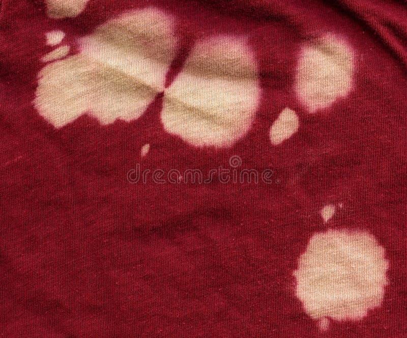 Bomullstyg texturerar - rött med blekmedelfläckar arkivfoton