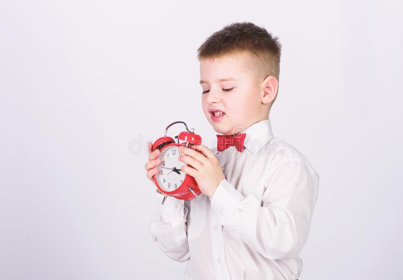 Kid adorable boy white shirt red bow tie. Develop self discipline. Set up alarm clock. Child little boy hold red clock. It is time. Schedule and timing royalty free stock images